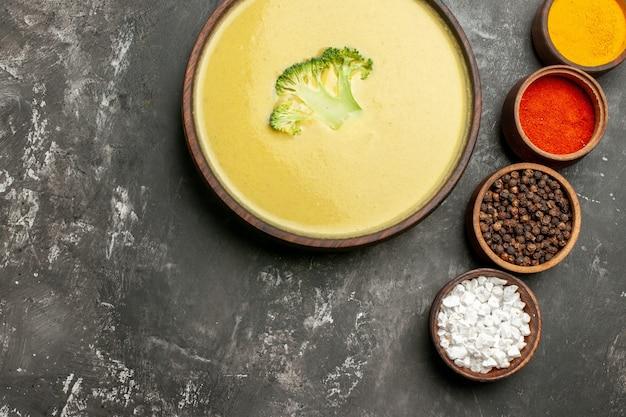 Visão horizontal de sopa cremosa de brócolis em uma tigela marrom e especiarias diferentes na mesa cinza
