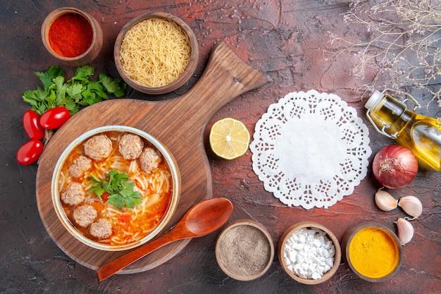Visão horizontal de sopa de almôndegas de tomate com macarrão em uma tigela marrom e diferentes especiarias. garrafa de óleo cebola alho e guardanapo em fundo escuro