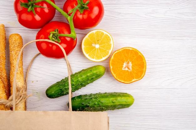 Visão horizontal de tomates frescos com pepino caule de limão no fundo branco
