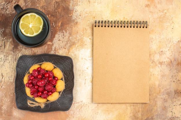 Visão horizontal de um bolo de presente com framboesas e uma xícara de chá com limão e caderno