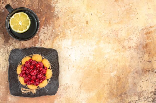 Visão horizontal de um bolo de presente com framboesas e uma xícara de chá com limão em uma bandeja marrom