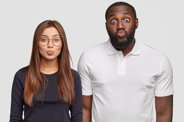 Visão horizontal de um homem e uma mulher inter-raciais de aparência agradável mantendo os lábios redondos