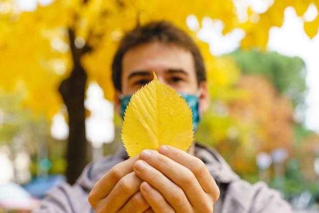Visão horizontal de um homem irreconhecível segurando uma folha amarela de outono.