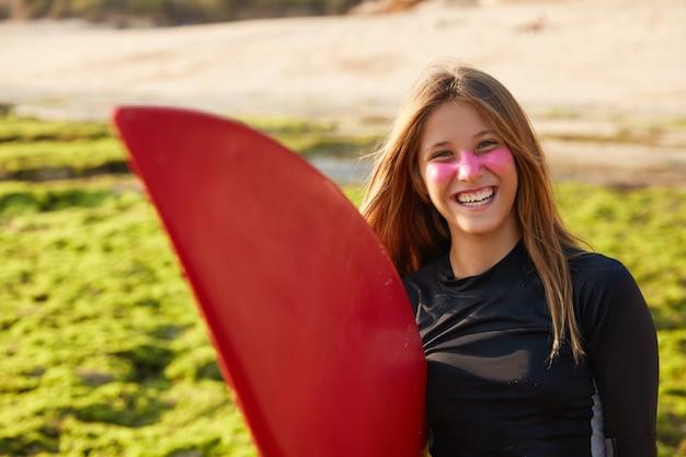 Visão horizontal de uma mulher alegre e ativa com uma prancha de surf, sorri feliz, segura a prancha, posa ao ar livre, vestida com blusa preta