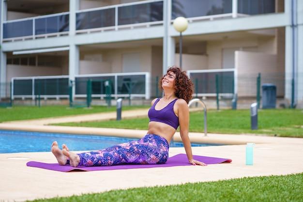 Visão horizontal de uma mulher caucasiana, respirando ao ar livre e fazendo exercícios no verão ao lado de uma piscina. estilo de vida fitness, exercícios e hábitos saudáveis ao ar livre.