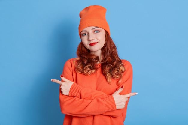 Visão horizontal de uma senhora vestida com roupas casuais, sorri agradavelmente, mantém as mãos cruzadas e aponta com os dedos indicadores de ambos os lados