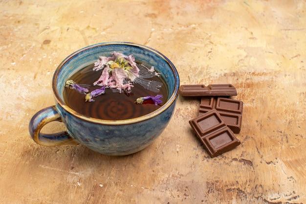Visão horizontal de uma xícara de chá quente de ervas e barras de chocolate na mesa de cores mistas