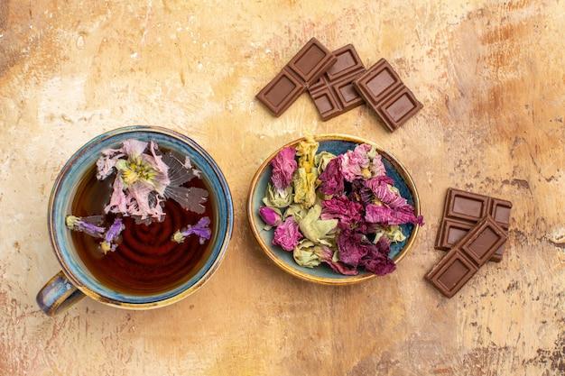 Visão horizontal de uma xícara de flores quentes de chá de ervas e barras de chocolate na mesa de cores mistas