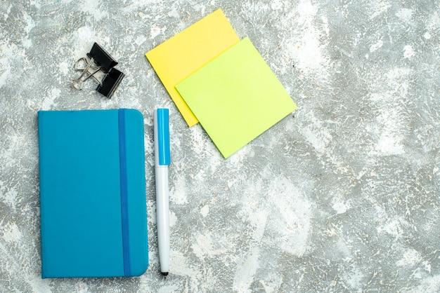 Visão horizontal do caderno azul fechado e papéis de anotação coloridos com caneta sobre fundo branco