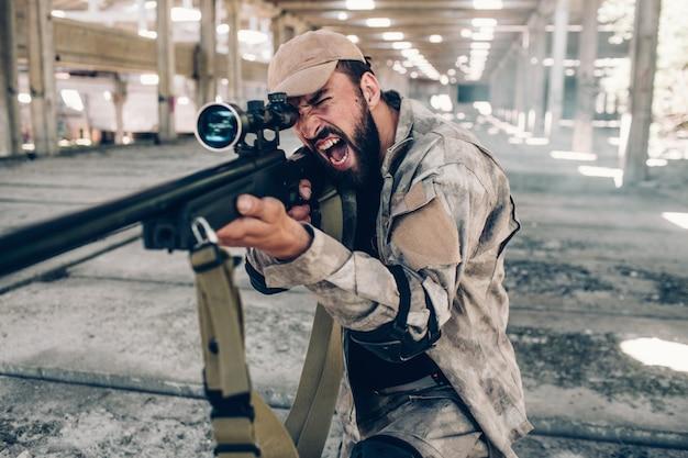 Visão horizontal do soldado militar, gritando e gritando. ele está mirando usando rifle grande. homem veste uniforme militar. ele está pronto para lutar e atirar.