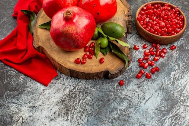 Visão lateral de close-up de romãs com uma tigela de sementes de romãs com folhas verdes