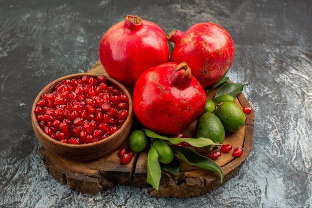 Visão lateral de close-up de romãs maduras e frutas cítricas com folhas no quadro