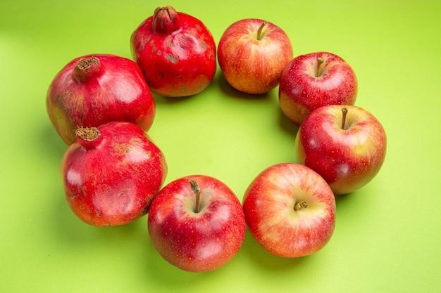 Visão lateral de frutas distantes, romãs vermelhas maduras e maçãs na superfície verde