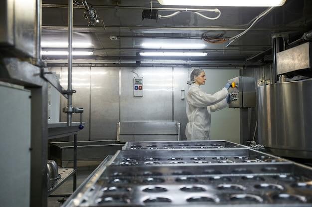 Visão lateral de grande angular em unidades de máquina operando jovem trabalhadora na fábrica de produção de alimentos limpos, copie o espaço