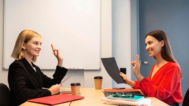 Visão lateral de mulheres de negócios usando linguagem de sinais