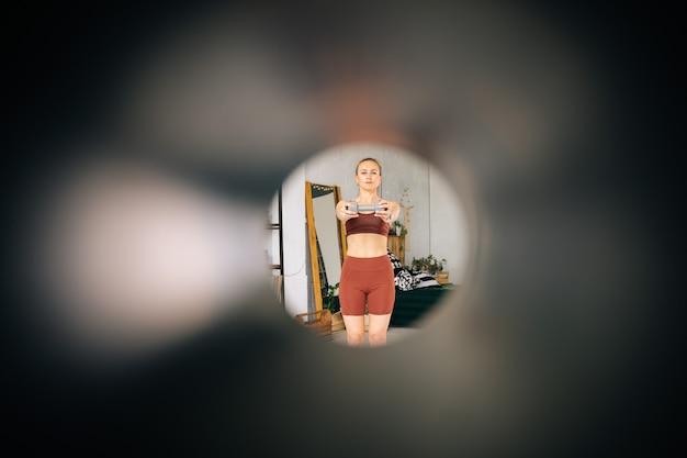 Visão limitada de jovem apto com corpo atlético perfeito vestindo roupas esportivas, exercitando-se durante o treinamento de treino. conceito de estilo de vida saudável e atividade física em casa.