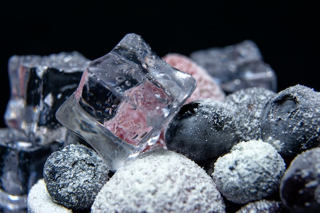 Visão macro de frutas congeladas: morango, mirtilo com cubos de gelo no fundo escuro