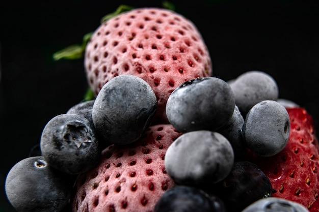 Visão macro de frutas congeladas: morango, mirtilo com cubos de gelo