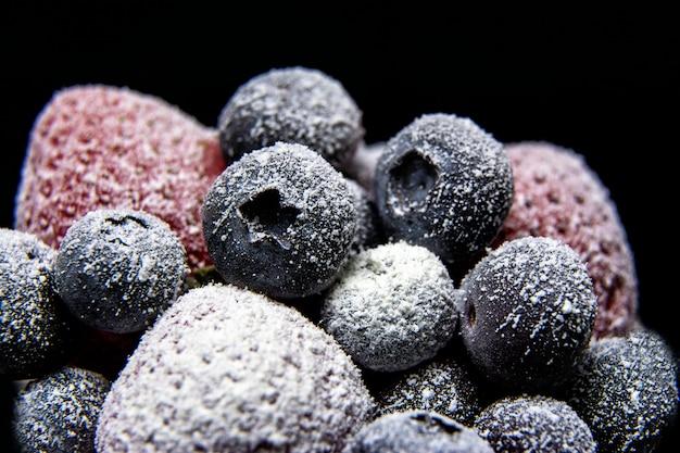 Visão macro de frutas congeladas: morango, mirtilo em fundo escuro