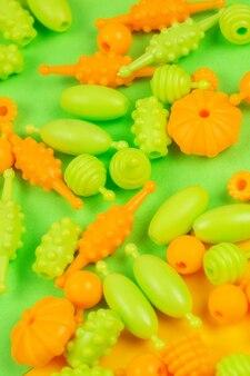 Visão macro de miçangas para a criatividade infantil, você pode fazer pulseiras, colares e anéis em um fundo verde