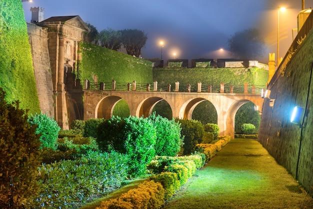 Visão noturna com luz e iluminação do castillo de montjuic na montanha montjuic em barcelona, espanha