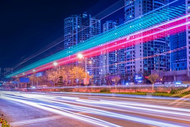 Visão noturna da estrada urbana e luzes do carro difusa