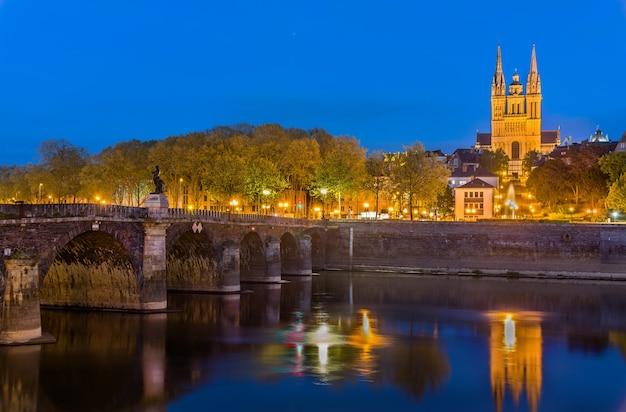 Visão noturna de angers com a ponte verdun e a catedral de saint maurice na frança