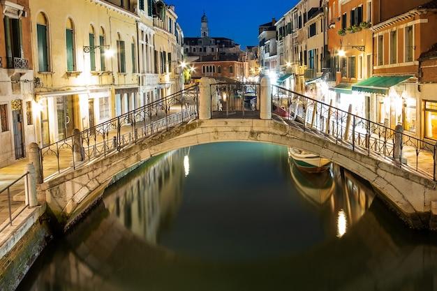 Visão noturna de arquitetura antiga iluminada, barcos flutuantes e reflexos de luz nas águas dos canais em veneza, itália