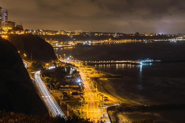 Visão noturna de carros em uma rodovia próxima ao oceano