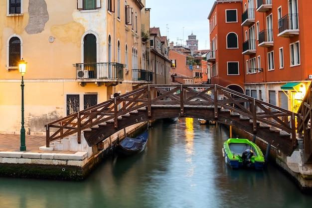Visão noturna de edifícios antigos iluminados, barcos flutuantes e reflexos de luz na água do canal em veneza, itália