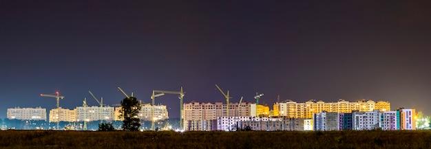 Visão noturna de panorama de muitos guindastes de construção no canteiro de obras da nova área residencial moderna