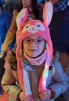 Visão noturna de uma menina sorridente com um chapéu rosa com orelhas iluminadas no natal em toledo, espanha