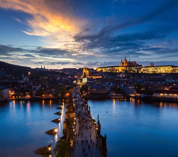 Visão noturna do castelo de praga e ponte carlos sobre o rio