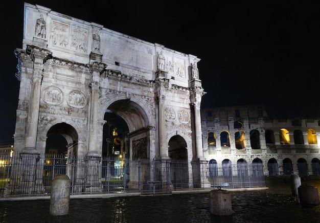 Visão noturna do coliseu e do arco de constantino em roma, itália.