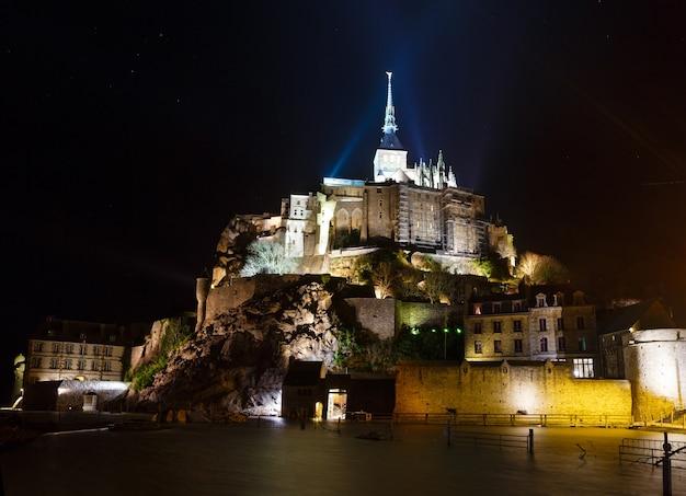 Visão noturna do mont saint-michel. a fachada principal da igreja construída no século xii. arquiteto william de volpiano.