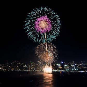 Visão noturna e fogo de artifício na praia de pattaya, tailândia