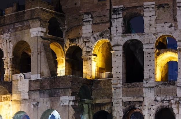 Visão noturna externa do coliseu (símbolo da roma imperial), itália.