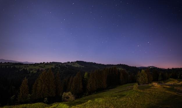 Visão noturna hipnotizante de colinas verdes e florestas de coníferas contra um céu azul estrelado e luas brilhantes