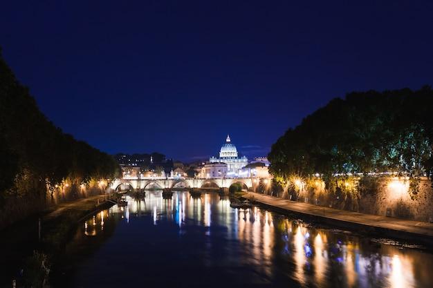 Visão noturna romântica da paisagem urbana de roma. panorama com a basílica de são pedro e o castelo e a ponte de santo ângelo. destino turístico famoso com o tibre. viaje com paisagem iluminada na itália, europa. Foto Premium