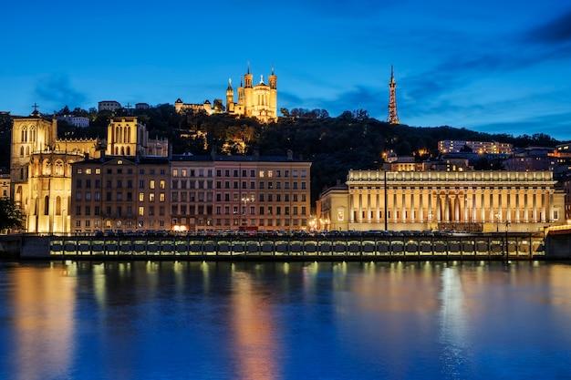 Visão noturna sobre o rio saône para a catedral fourviere na cidade de lyon.