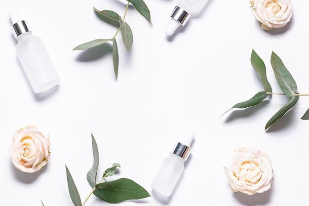 Visão plana e criativa de cima de soros naturais para cuidados com a pele em frascos de vidro branco, lindas flores rosas e galhos de eucalipto frescos