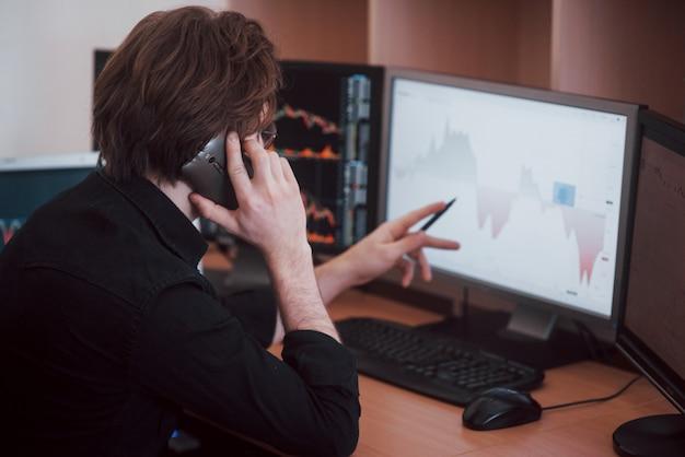 Visão por cima do ombro e corretor da bolsa negociando on-line enquanto aceita pedidos por telefone. várias telas de computador cheias de gráficos e análises de dados