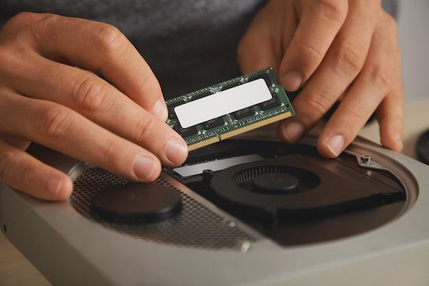 Visão próxima em mãos profissionais removendo a placa de memória para atualizar o pequeno computador pessoal