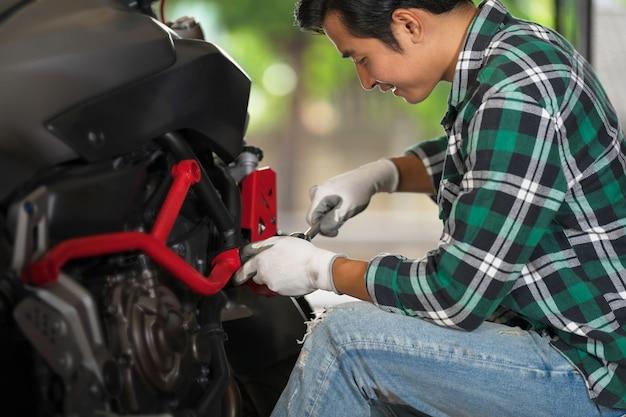 Visão recortada do mecânico de motocicleta usando uma chave e soquete em uma motocicleta