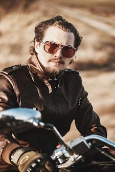 Visão séria do homem barbudo âncora na jaqueta de couro e óculos vermelhos na motocicleta.