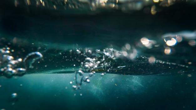 Visão subaquática de bolhas de ar flutuando até a superfície na água do mar.