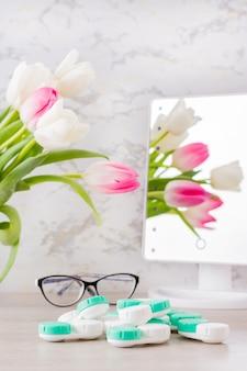 Visão subnormal e a escolha entre óculos e lentes. uma pilha de recipientes para lentes e óculos em frente a um espelho sobre a mesa. visão vertical
