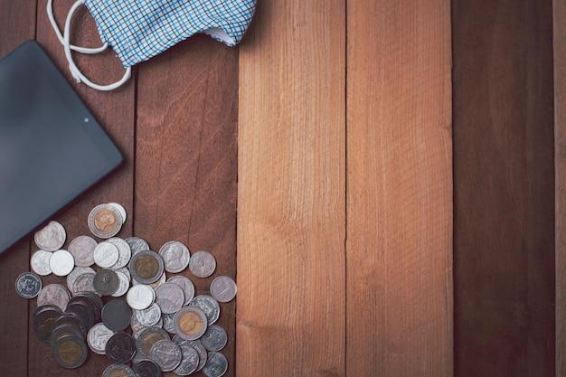 Visão superior do conceito de dinheiro e finanças, enquanto a situação de covid-19 inclui mesk, tablet e moeda de fundo de madeira