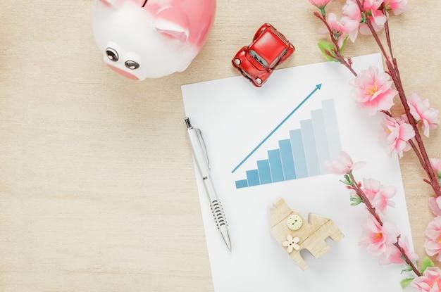 Visão superior do conceito de mesa do escritório de negócios. poupar dinheiro com resumo de gráficos. casa de madeira também carro e relógio em prateleira de madeira. a linda flor rosa com caneta em fundo de madeira com espaço de cópia.