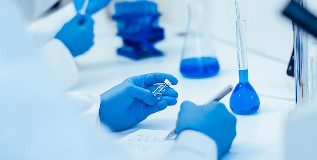 Visão traseira. cientista registrando os resultados das investigações em um jornal de laboratório